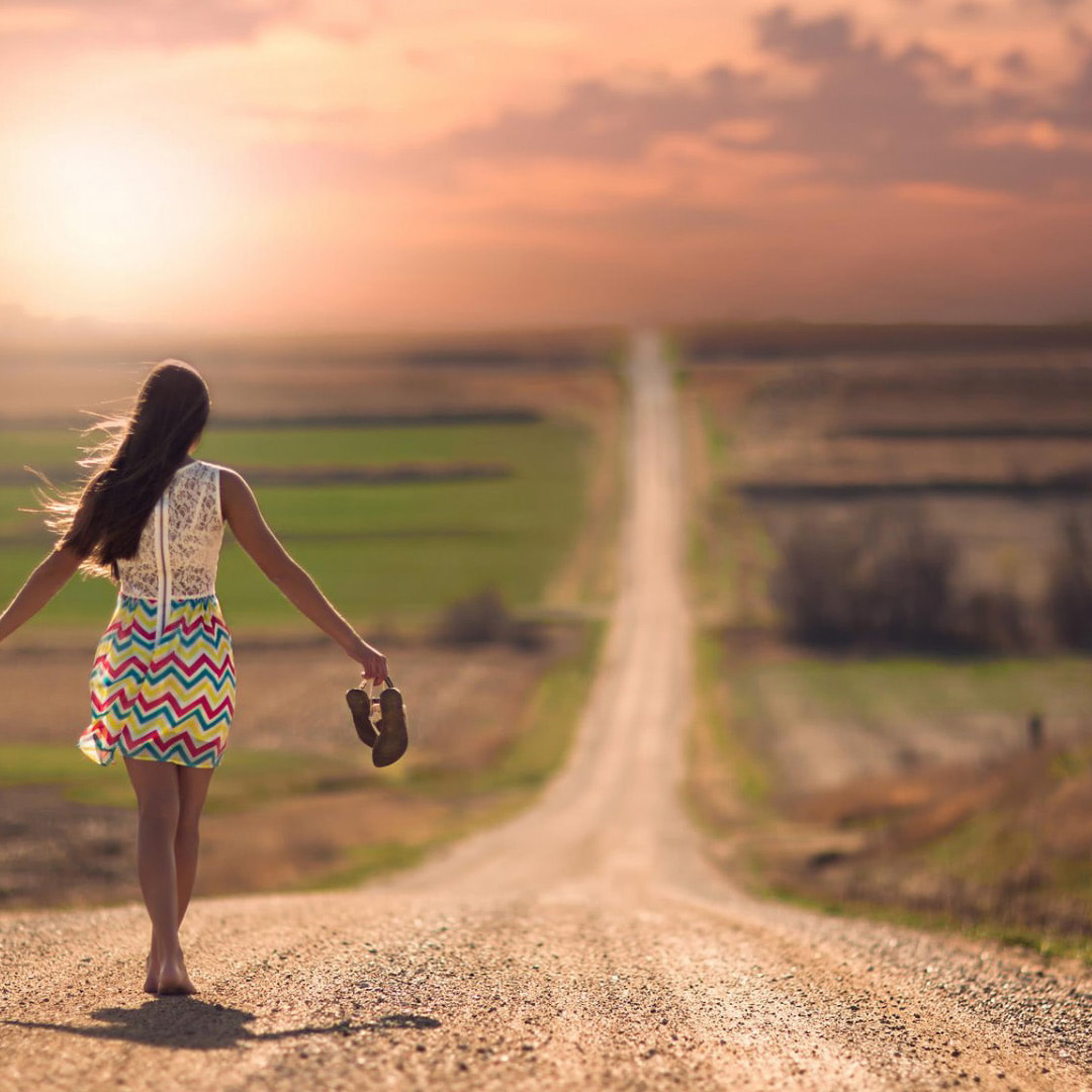 Woman with shoes off walking down a dirt road after Spiritual Life Coaching